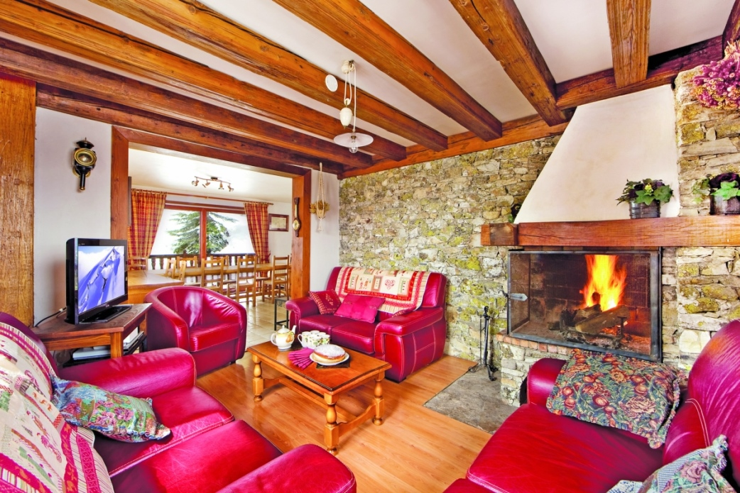 Ski Total | Chalet Chenus lounge area with burning fire place