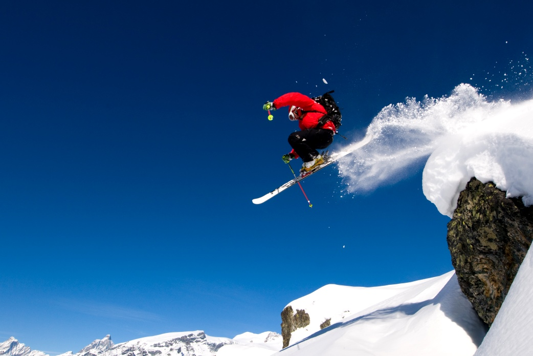 Ski Total | A skiier jumps from a small cliff off piste