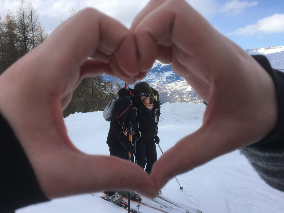 Ski Total | Two skiers kissing within a love heart