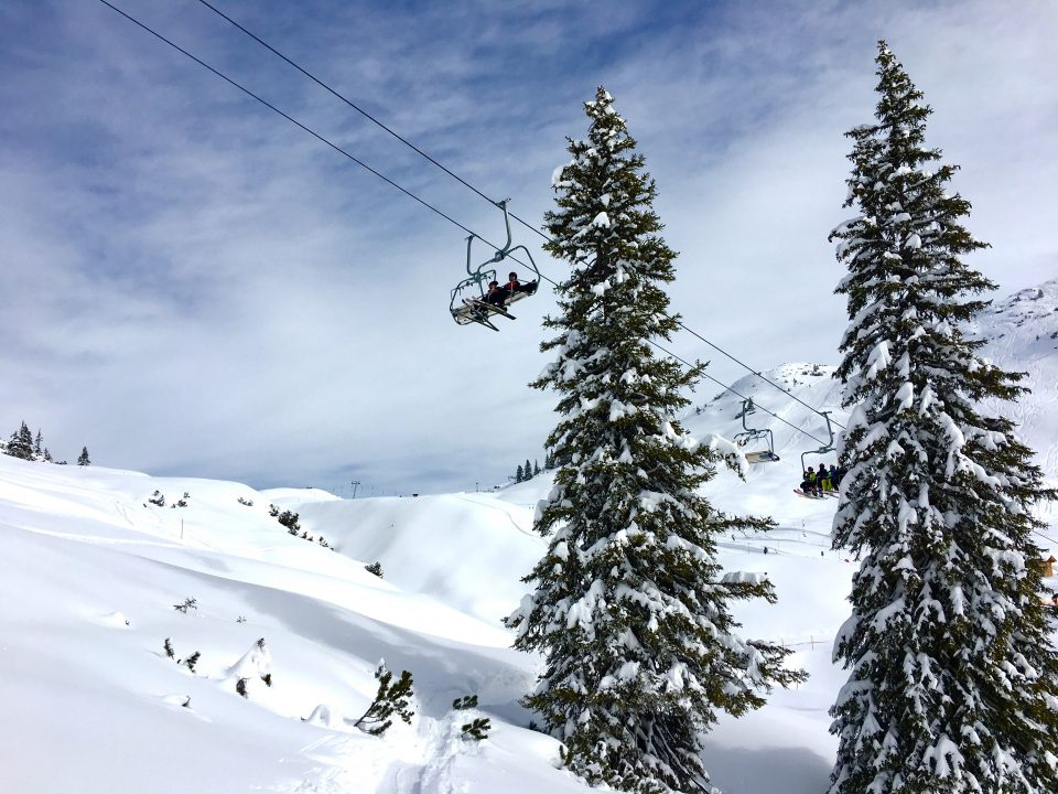 Ski Total | blue skies, snow, trees and people on a chair lift