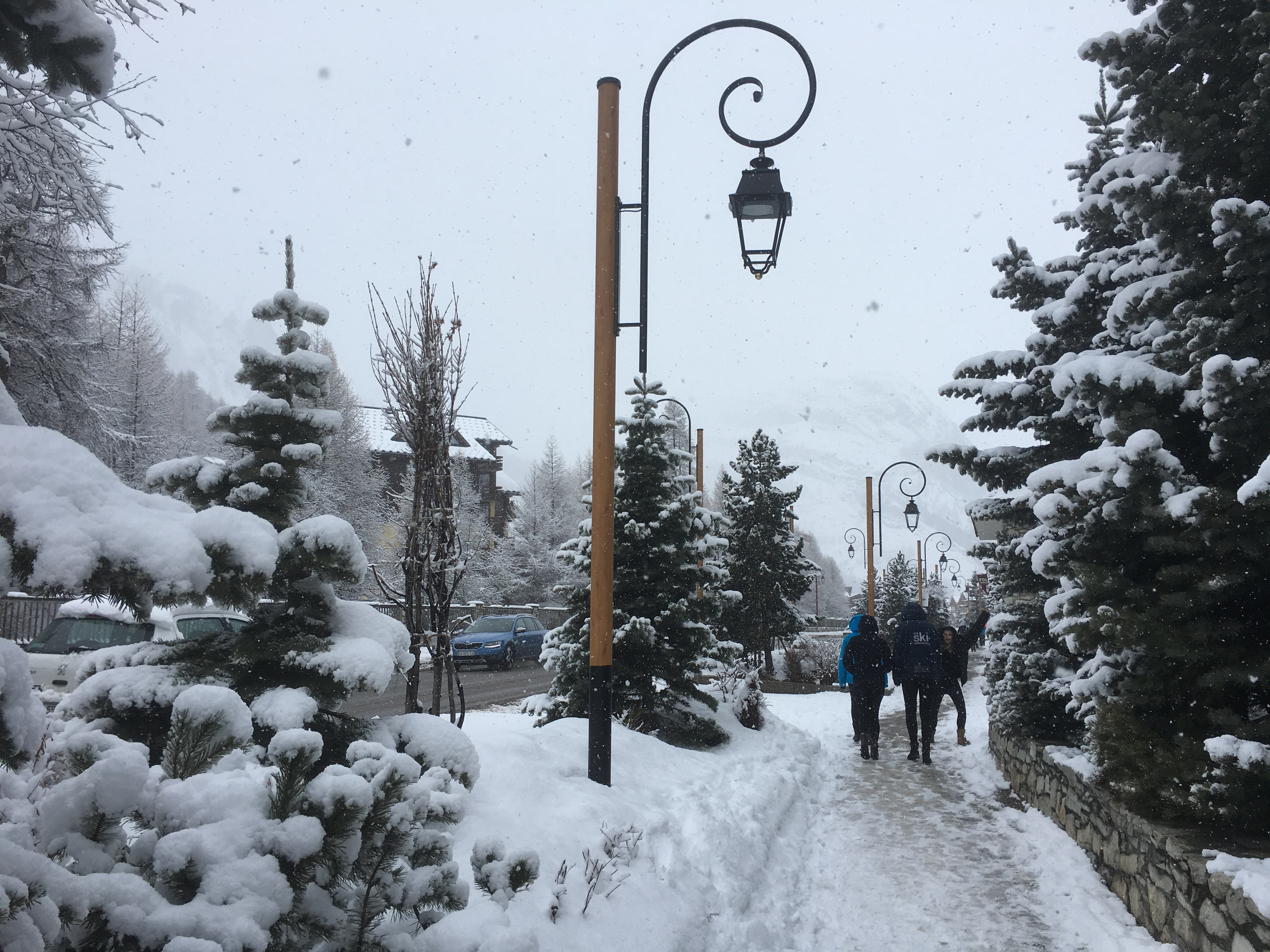 Ski Total | Snowy scenes in val d'Isere - trees coated in snow and people walking down a snowy street