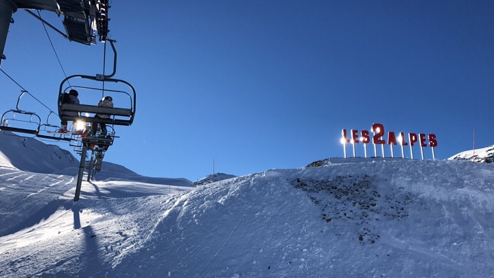 Ski Total | skiers on a ski lift next to the Les Deux Alpes sign